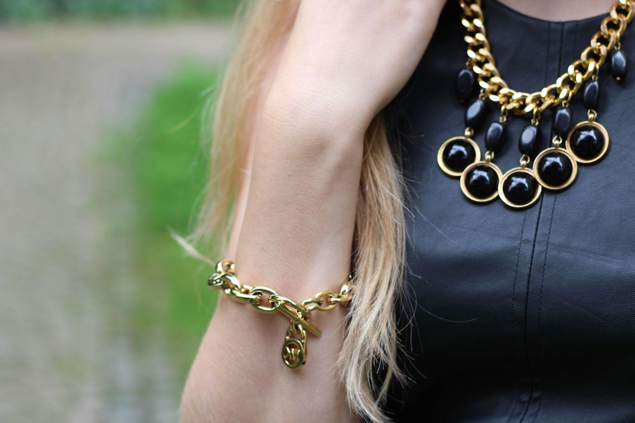 Schwarzes Lederkleid mit goldenen Schmuck goldenes Armband Michael Kors