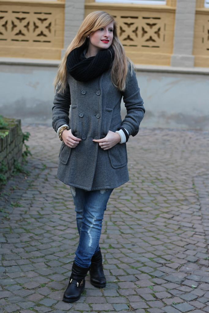 Herbstlook Grauer Mantel mit Biker Boots und Ripped Jeans mit schwarzer Rundschal Winteroutfit