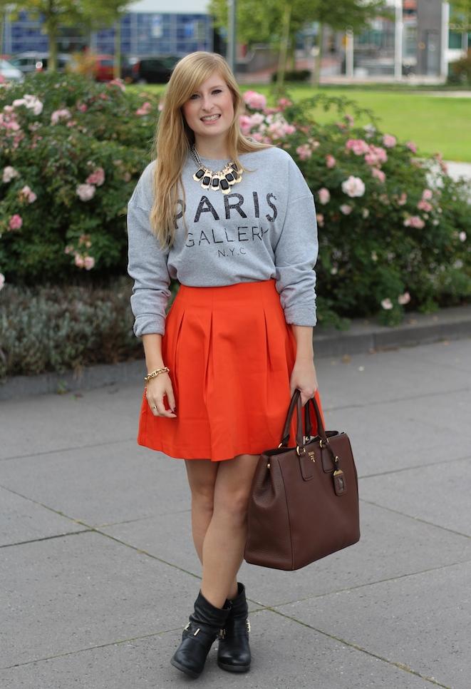 Outfit grauer Pullover mit Print und oranger Minirock braune Prada Tasche schwarze Boots