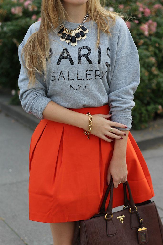 Grauer Pullover mit Print und oranger Rock mit Prada Tasche