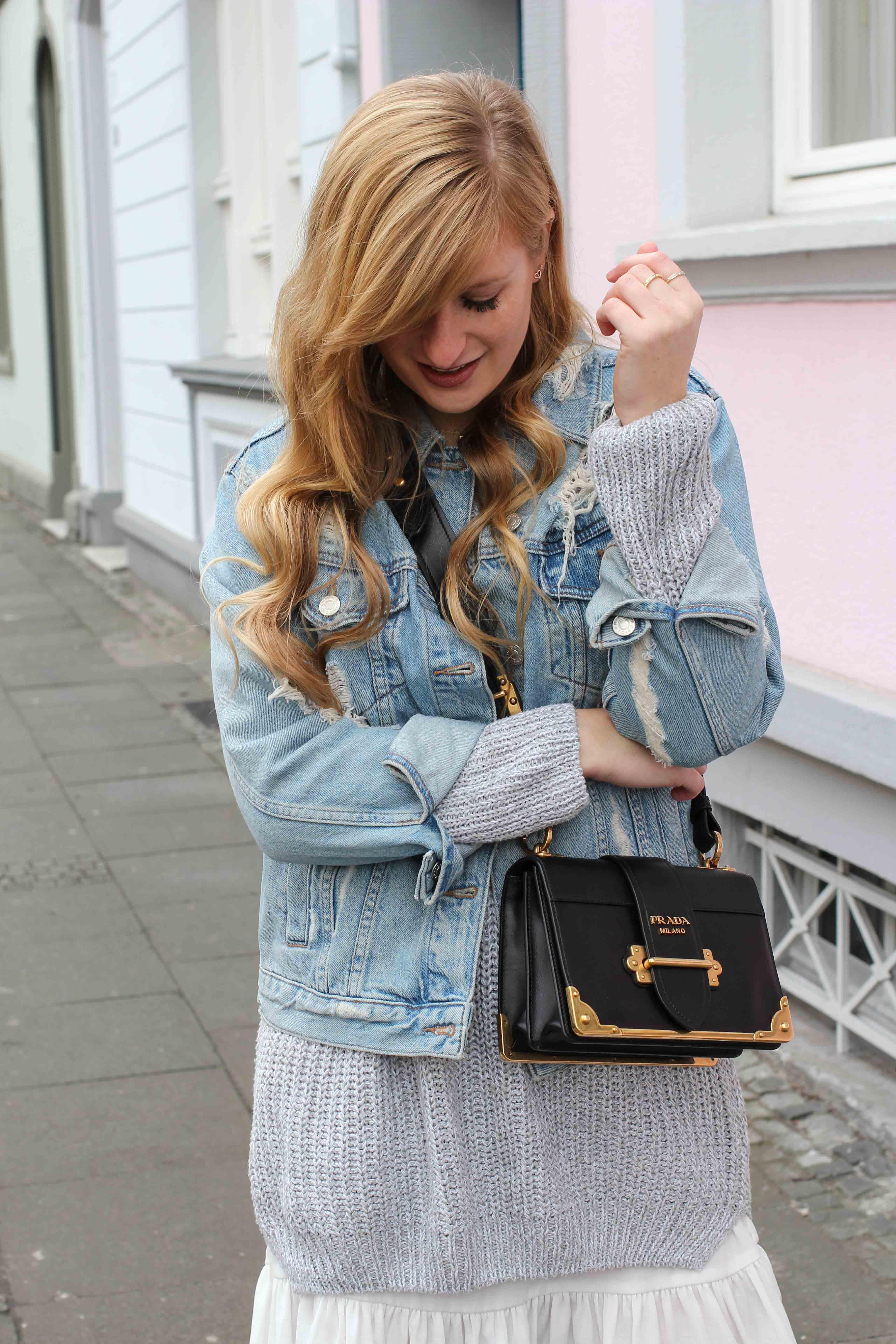 Winter Layering mit Kleid grauer Pullover Outfit zerrissene Jeansjacke Prada Cahier Bag Designertasche Streetstyle Modeblog Bonn Fashion Blog Deutschland