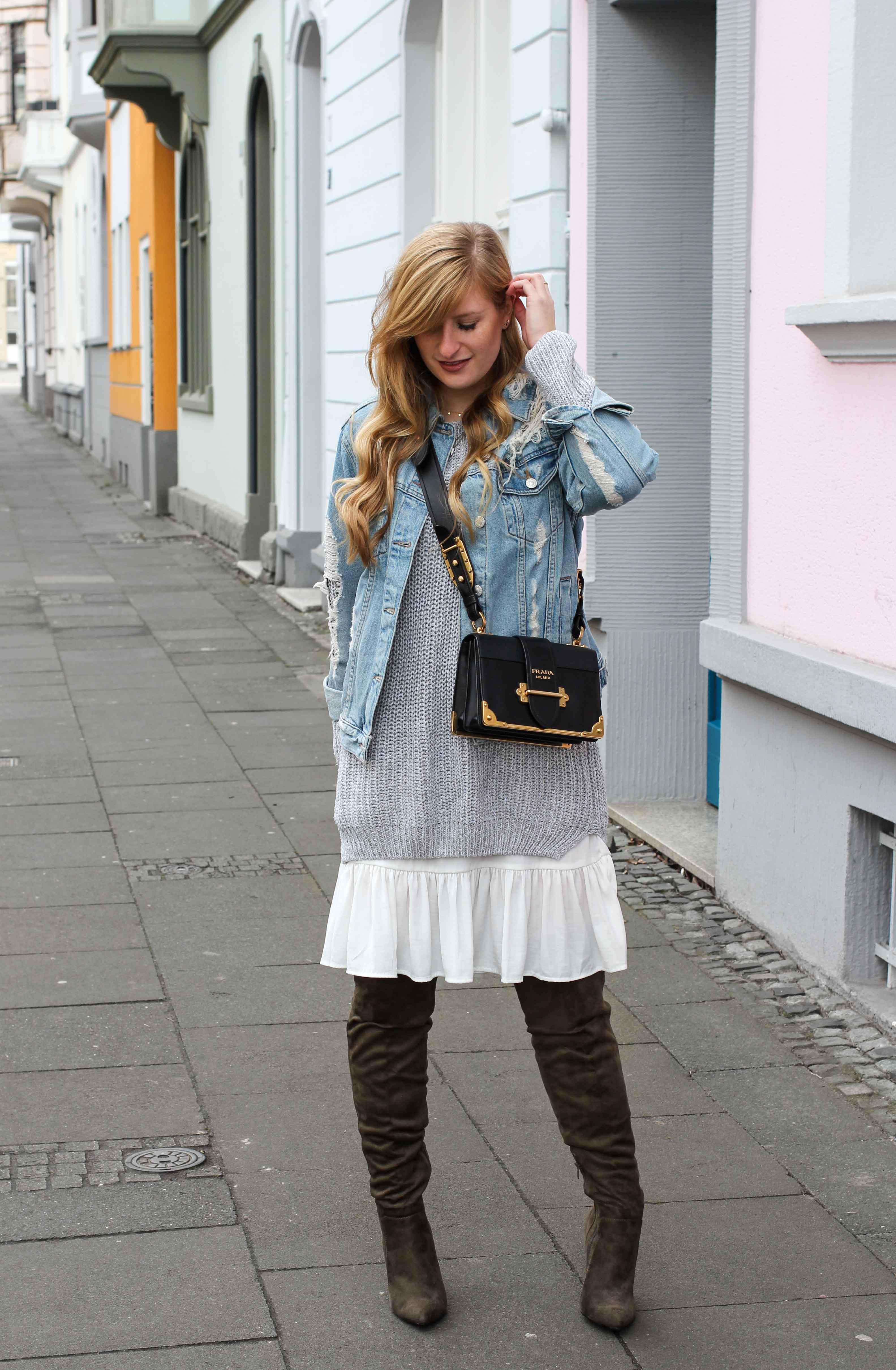 Winter Layering mit Kleid grauer Pullover grüne Overknees Outfit zerrissene Jeansjacke Prada Cahier Bag Designertasche Streetstyle Modeblog Bonn Fashion Blog Deutschland