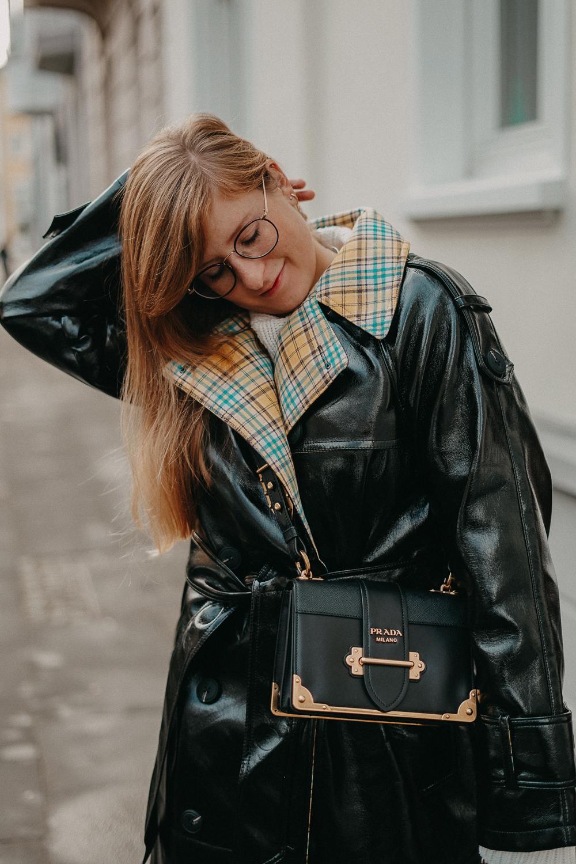 Schwarzer Vinyl Trenchcoat kariertem Futter kombinieren Outfit Modeblog Winter Pomsky Streetstyle Bonn Prada Cahier