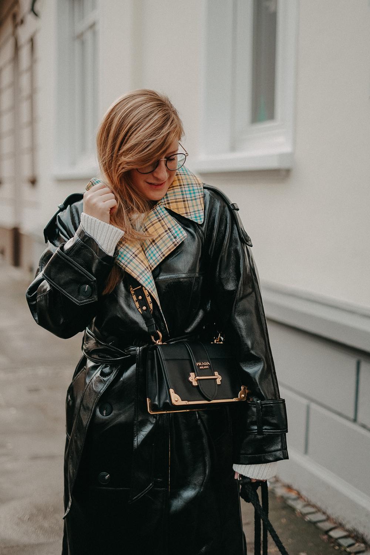 Schwarzer Vinyl Trenchcoat kariertem Futter kombinieren Outfit Modeblog Winter Pomsky Streetstyle Bonn Prada Cahier Designertasche